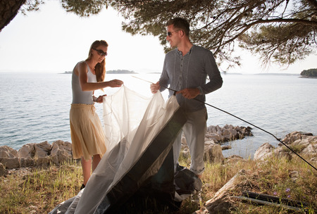 Couple putting up tent by sea LANG_EVOIMAGES