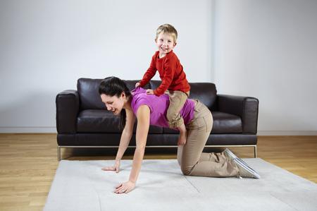 Mother giving boy a piggyback ride