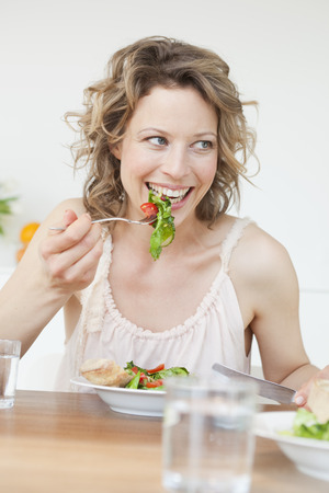 womanly: Woman eating mixed salad on table LANG_EVOIMAGES