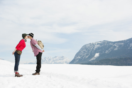 smooching: Couple kissing in front Alps LANG_EVOIMAGES