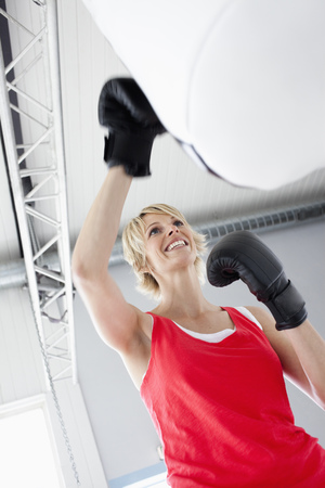 punched out: Woman boxing punching bag