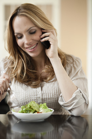 Woman on cellphone eating salad