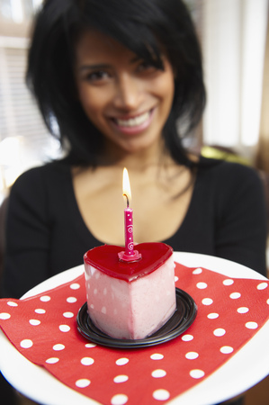 rejoices: Woman holding a heart shaped cake LANG_EVOIMAGES