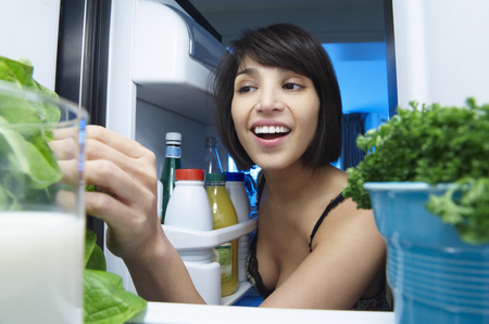 Woman looking into the fridge LANG_EVOIMAGES