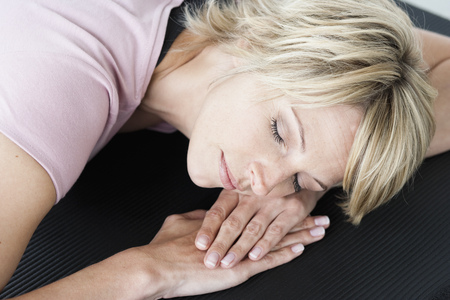 doze: Woman relaxing on yoga mat