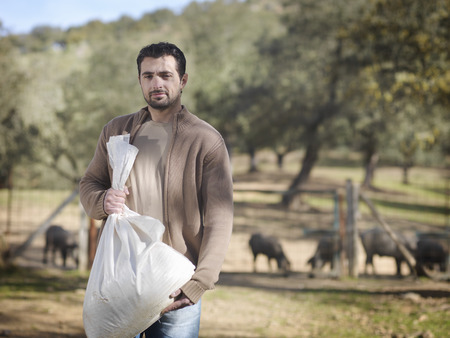 Man on farm holding bag of cattle feed