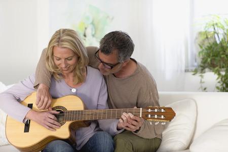Man and woman strumming guitar LANG_EVOIMAGES