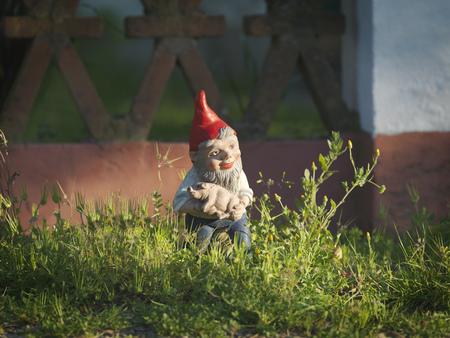 summers: Garden gnome holding piglet