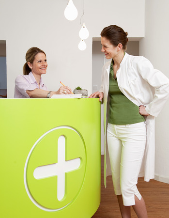 Doctor and receptionist in surgery LANG_EVOIMAGES