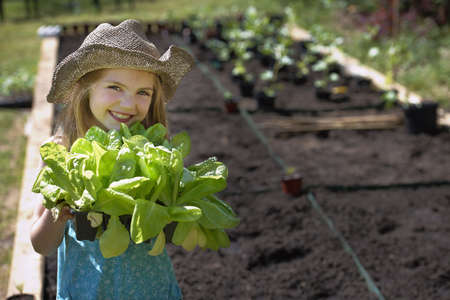 seeding: Young girl planting vegetables
