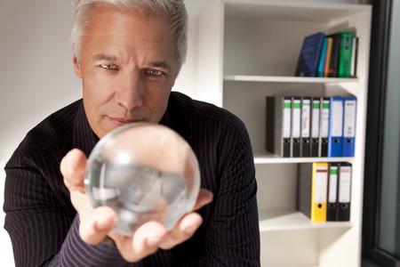 hocus pocus: Businessman holding a crystal ball LANG_EVOIMAGES