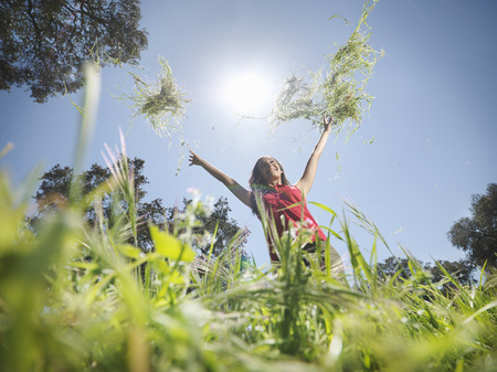 Woman throwing grass in the air LANG_EVOIMAGES