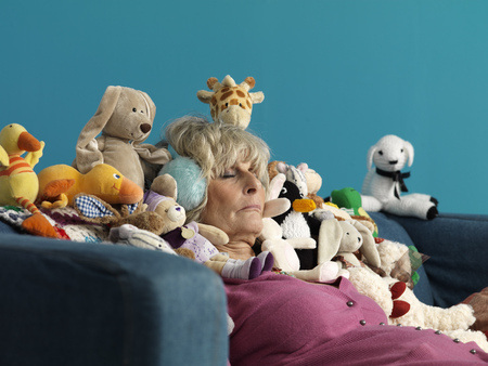 Mature woman asleep surrounded by toys