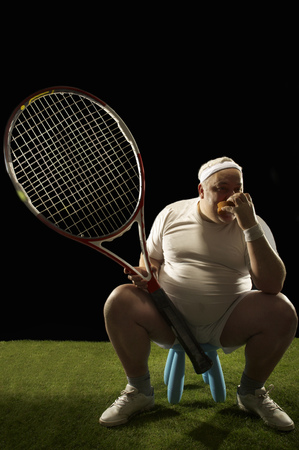 Tennis player with large racquet sitting LANG_EVOIMAGES