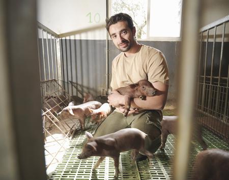 Man in pig pen holding piglet LANG_EVOIMAGES