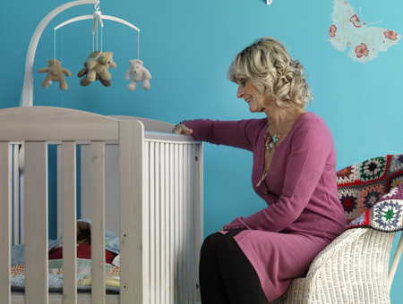 generation gap: Mature woman sitting next to cot