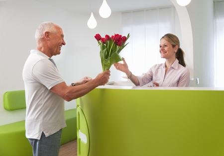 generosidad: Paciente agradeciendo a la recepcionista LANG_EVOIMAGES