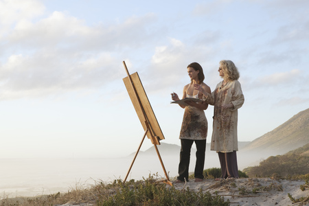Woman teaching young man how to paint LANG_EVOIMAGES