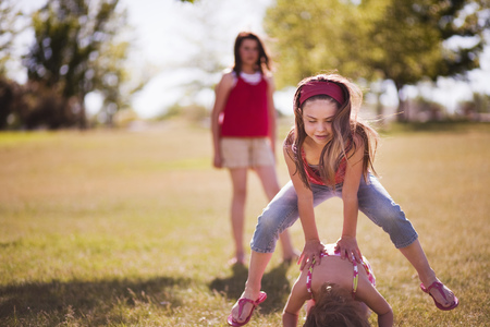 3 girls playing leap frog in park