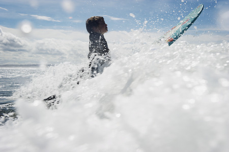 Young boy surfing through waves LANG_EVOIMAGES
