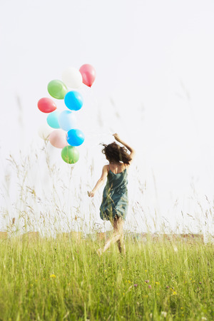 Woman with balloons running away LANG_EVOIMAGES