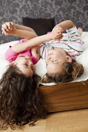 Mädchen, die im Bett der Eltern heraus hängen LANG_EVOIMAGES