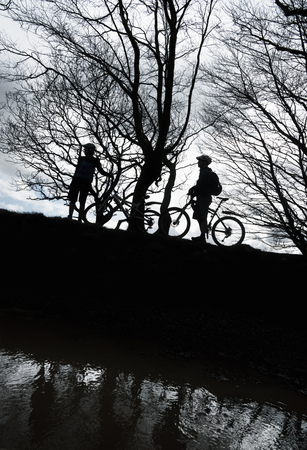 truelove: Silhouette couple biking in countryside LANG_EVOIMAGES