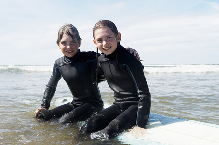 Children sitting on surf board in the se