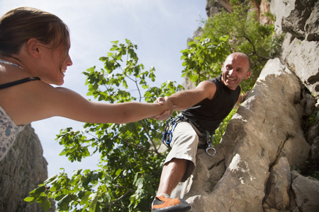 taught man: Rock climber helping partner