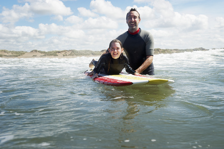 Father and daughter surfing in the sea LANG_EVOIMAGES