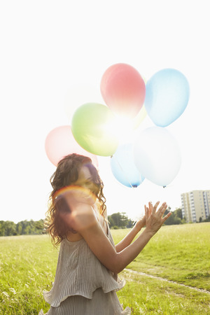 Woman with air balloons in meadows