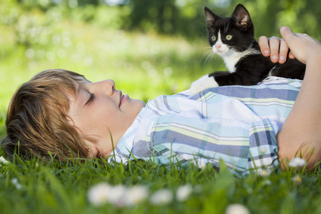 lays down: Boy in meadow hugging a cat LANG_EVOIMAGES