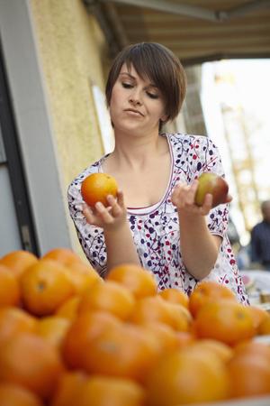 levantar peso: Joven en un puesto de frutas