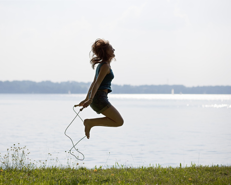 blue waters: Girl jumping with rope LANG_EVOIMAGES