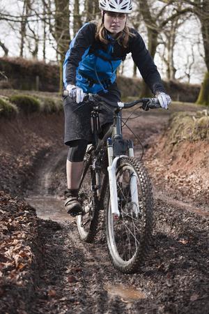 dirtied: Woman riding mountain bike muddy track