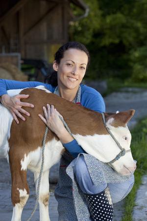 Farmwoman hugging calf