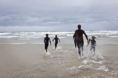 pas: Family running in to the sea in wetsuits