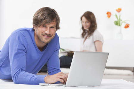lays down: Man on laptop while woman reads