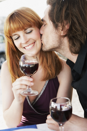 sipping: Man kissing woman on cheek