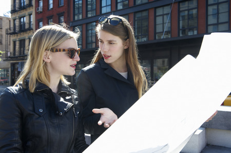 interrogations: Women walking in the street with a map LANG_EVOIMAGES