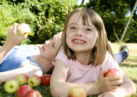 Happy girl and friend with apples
