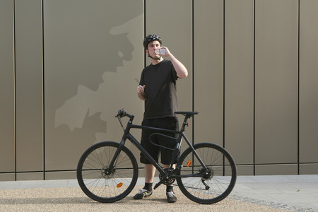 ceased: Man with bicycle drinking water LANG_EVOIMAGES