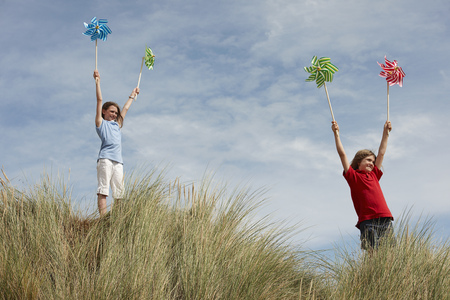wind blown: Girls holding windmills up in the sky LANG_EVOIMAGES