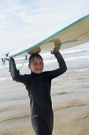 summers: Young boy with surf board on his head
