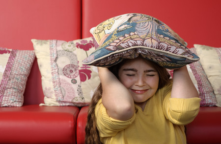 concealing: Young girl hiding under cushion