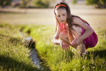 agachado: Niña jugando en el arroyo