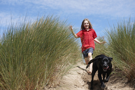 pursuing: Young Girl Chasing dog in sand dunes LANG_EVOIMAGES