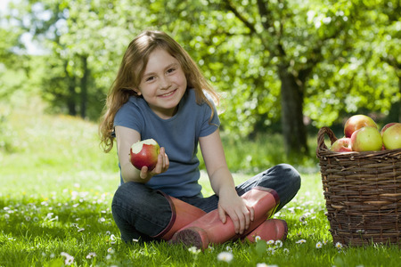morsels: Girl in meadow, eating apple LANG_EVOIMAGES
