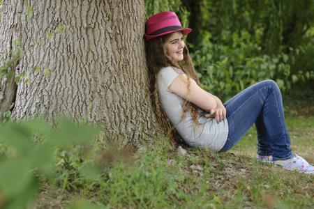 singularity: Girl in pink hat sitting against tree