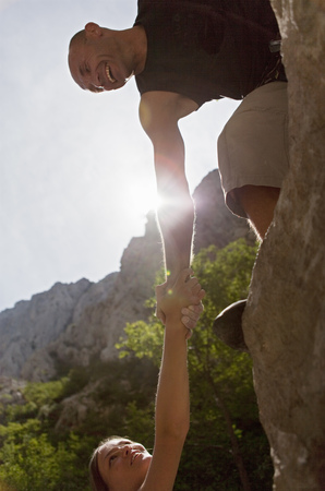 jeopardizing: Rock climber helping partner
